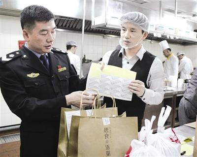 工作人员在摩尔城检查网络订餐配送环节的封口贴 摄影/本报记者 辛永红