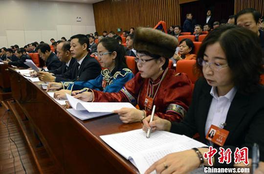 图为与会代表听取政府工作报告。 乌娅娜 摄