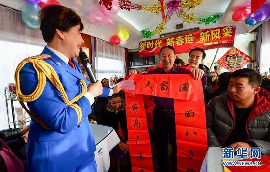 演员刘树芳向旅客送春联。