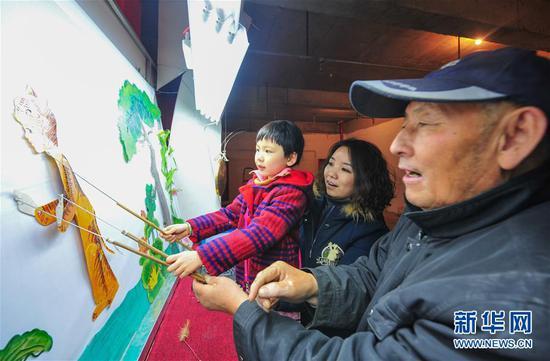 市民带着孩子在呼和浩特市大召文化庙会上体验皮影戏