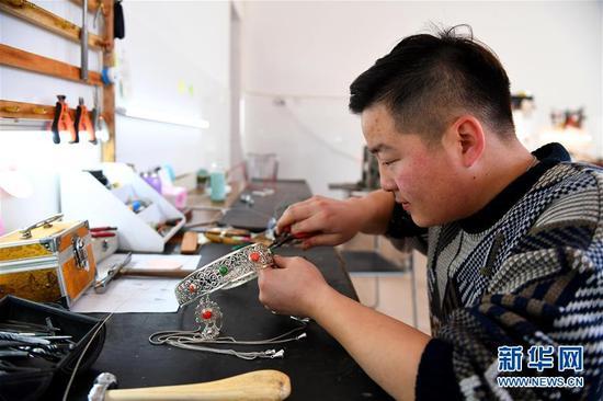 1月10日,蒙古族创业者钢巴图在克什克腾旗民族文化创新创业孵化基地创作蒙古族银饰。