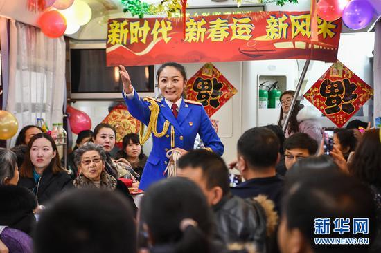 演员宋恋池在车厢里为旅客们表演魔术。