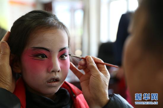 毕克齐镇腊铺村脑阁表演队在为即将进行的表演做准备,图为小演员上妆。