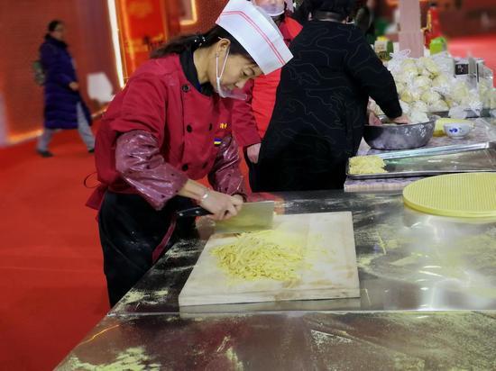 来自青城种养殖专业合作社的董瑞英在美食博览会现场切豆面。