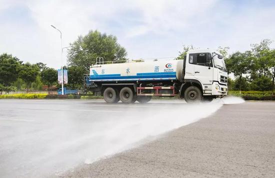 7月16日,洒水车在石嘴山市大武口区星光大道洒水作业。