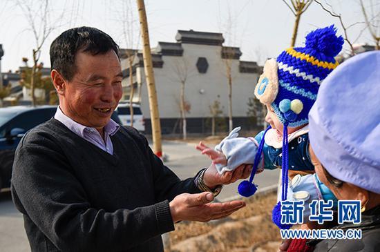马国权在润丰村的新家门前陪小孙子玩耍(2月18日摄)。新华社发(冯开华 摄)