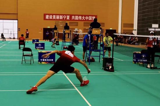 羽毛球选手王博喧在男子甲组预赛中救球。