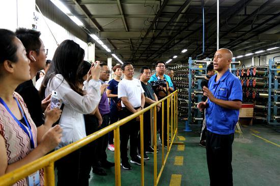 记者听取企业负责人关于钢帘线生产情况介绍。