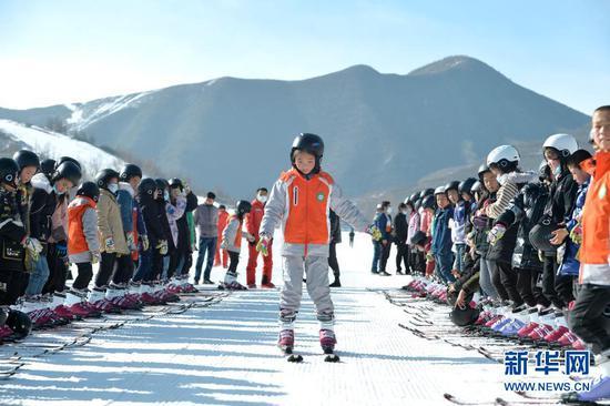 12月27日,在娅豪国际滑雪场内,滑雪爱好者在进行热身活动。