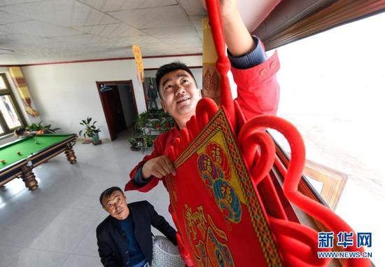 2月11日除夕当天,王涛(右)在为脱贫户刘玉强家挂中国结。