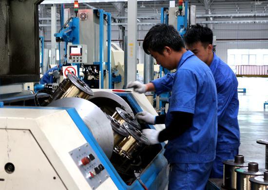 工人正在操作钢帘线生产设备。