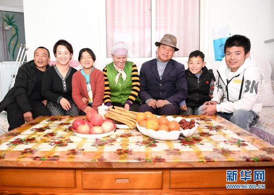 2月11日,张俊明(右三)一家人在滨河家园移民村的家里合影。