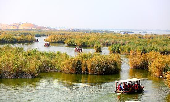 游客在沙湖景区乘船游玩。