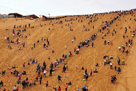 """游客在港中旅(宁夏)沙坡头旅游区""""沙漠区""""游玩。"""