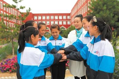 何桂琴(右三)和学生一起做游戏。记者 王玉平 摄