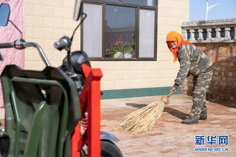 3月1日,宁夏灵武市白土岗乡海子井村,村民吴秀花在打扫新房的院子。