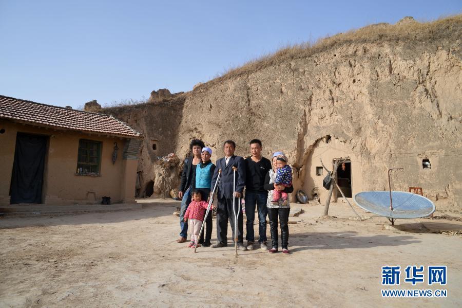 张俊明(中)一家人在固原市彭阳县红白阳镇自家的院子里合影(2013年6月15日摄)。