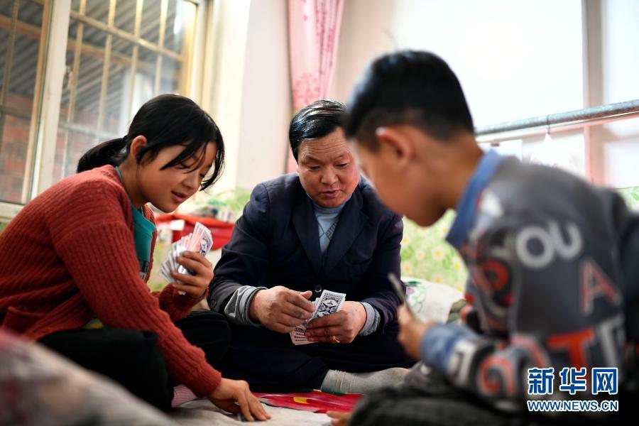 2月11日,张俊明在滨河家园移民村的家中与家人打扑克。