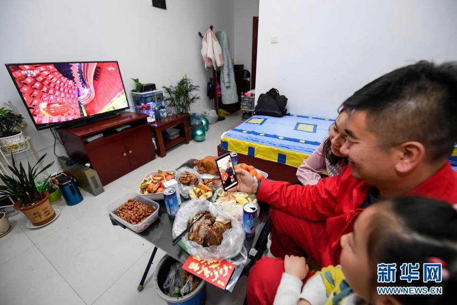 2月11日除夕夜,王涛(中)和妻子女儿在宿舍同在银川的父母和2岁的儿子通视频电话。