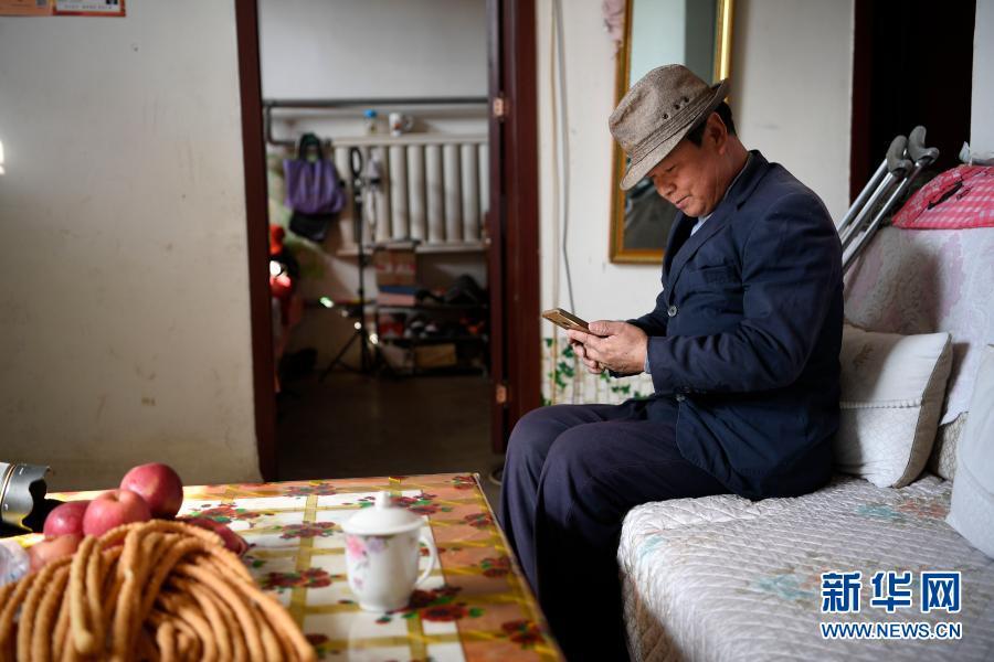 2月11日,张俊明在滨河家园移民村的家中翻看手机,准备网购一些家庭用品。
