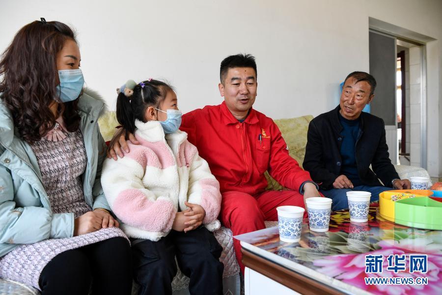 2月11日除夕当天,王涛(右二)和妻子女儿走访看望脱贫户刘玉强(右一)。刘玉强家过去住的是土房,2017年脱贫并盖了新房,2019年还开起了农家乐。