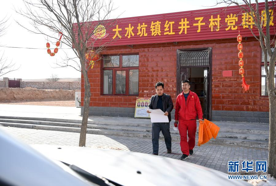 2月12日农历正月初一,王涛(右)和村副主任冯荣彬走出办公室,准备在村里流动广播宣传疫情防控知识。
