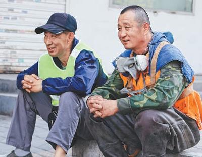 图为清掏工作结束后,王西平(右)和叶文东坐在路边休息。   本报记者 禹丽敏摄
