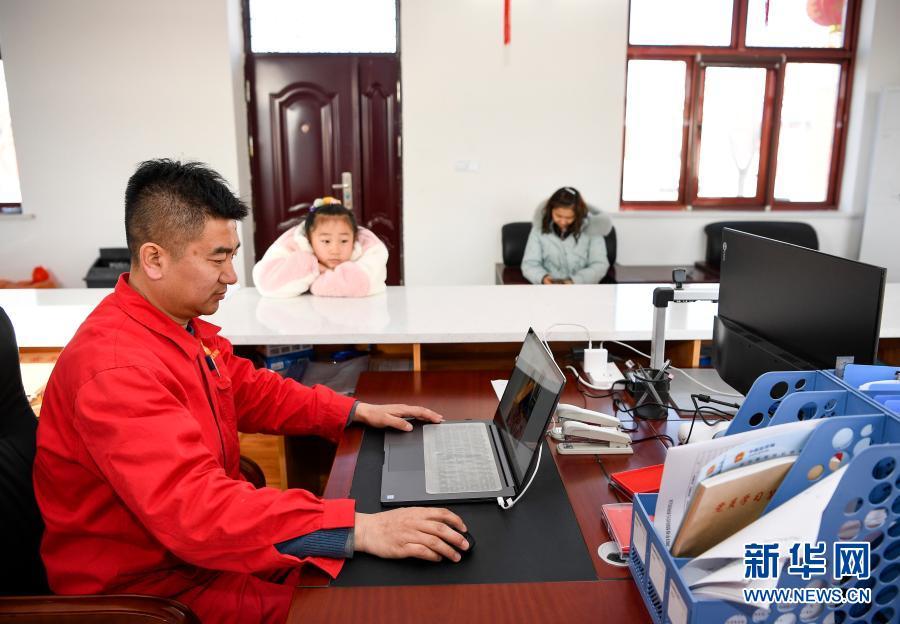 2月11日除夕当天,王涛(前)在办公室整理资料,妻子朱海燕和7岁的女儿王思淇在一旁等候。