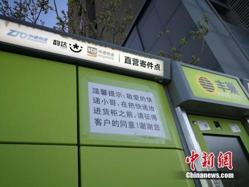 资料图:北京市某小区外的快递柜上张贴提示,提醒快递员放进货柜前首先征得收件人同意。中新网 邱宇 摄