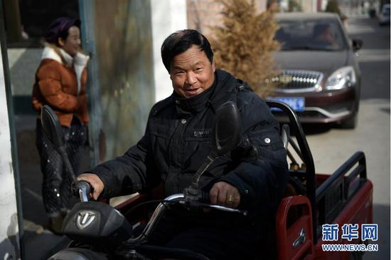 2月11日,张俊明准备骑着电动三轮车去滨河家园移民村的集市采购物品。