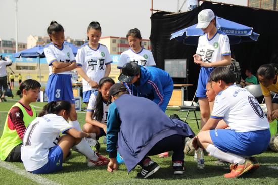 宁夏初中女子队球员们在认真听教练分析比赛