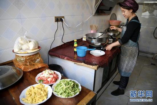2月11日,张俊明的儿媳在滨河家园移民村家中厨房里为家人准备午饭。