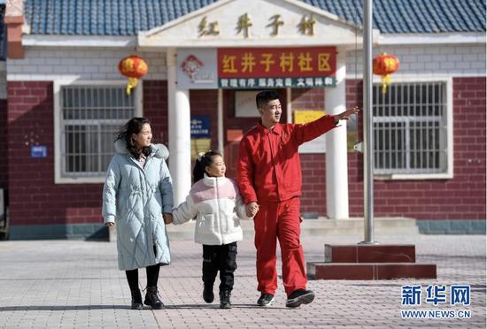 2月11日除夕当天,王涛在给妻子和女儿讲述红井子村的变化。