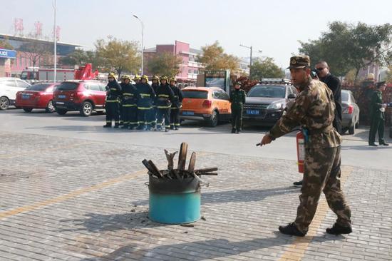消防官兵演示灭火器的正确使用方法