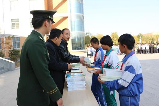 消防官兵向学生代表发放安全知识读本