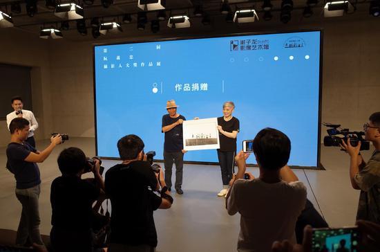 谢子龙影像艺术馆执行馆长卢妮代表谢子龙影像艺术馆上台接受作品捐赠
