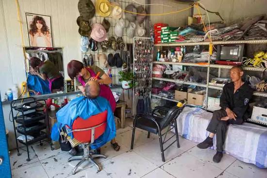 新疆奇台本地的一位姑娘开了一家理发店,同时售卖服装鞋帽等。