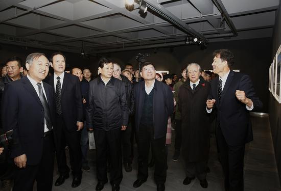 入选作者刘慎库(右1)向李前光(左2)、郑更生(左1)、张俊峰(左3)等领导和嘉宾介绍作品情况