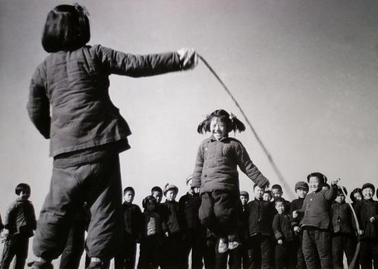 (1956年12月,河北省高阳县邢果庄村的小学生们在空地上跳绳-新华社稿)