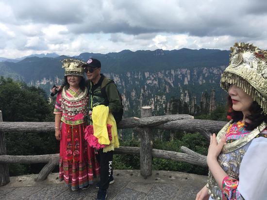 游客穿上民族服装在天子山景区留影