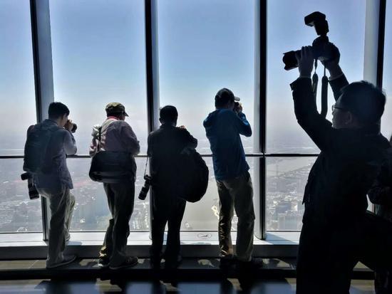 2018年5月11日,来自北京和上海摄影师在中国第一高楼上海中心大厦观光厅采访拍摄。钮一新 摄