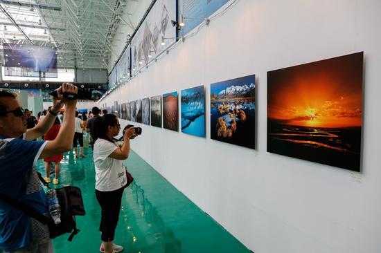 展览现场,人们纷纷举起相机,拍摄参展作品中记录的自然生态景观。