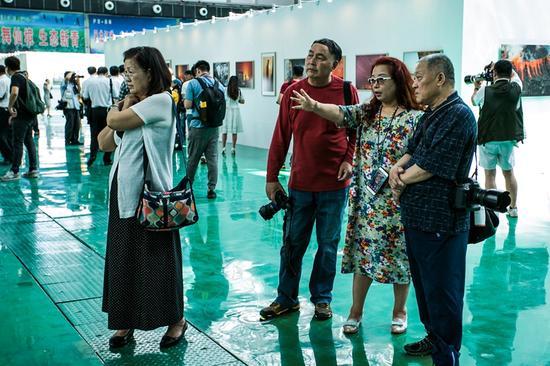 广大参展摄影家,一边观看展览,一边就参展作品品头论足。