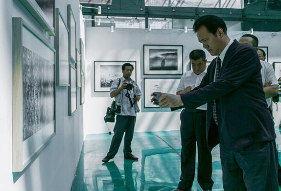 中国文联党组成员、副主席、书记处书记李前光(右一)一边看展,一边记录下精彩佳作。
