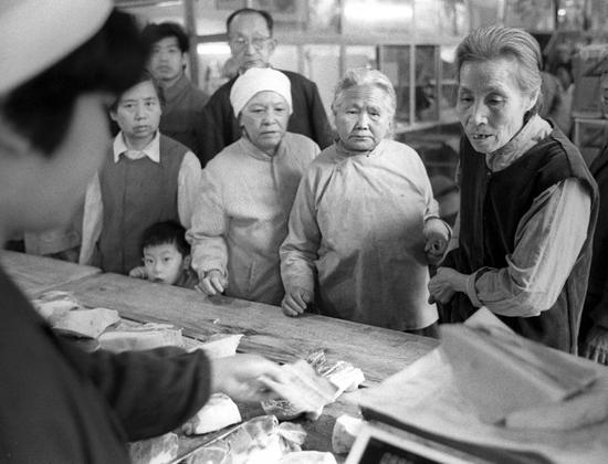 买肉的人群中有老人,也有带孩子来的妇女。