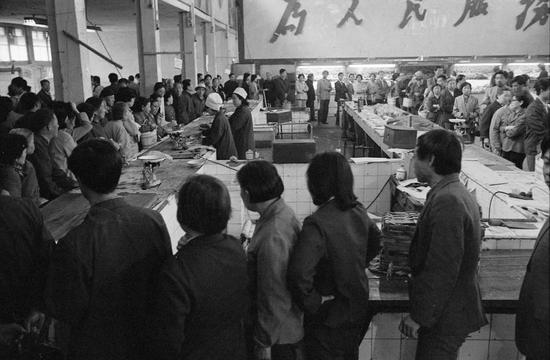 1988年5月15日早晨,北京市朝内菜市场大肉组售货员按原价定量供应生肉。市民纷纷涌入菜市场持北京市居民购货证和肉票排队抢购。