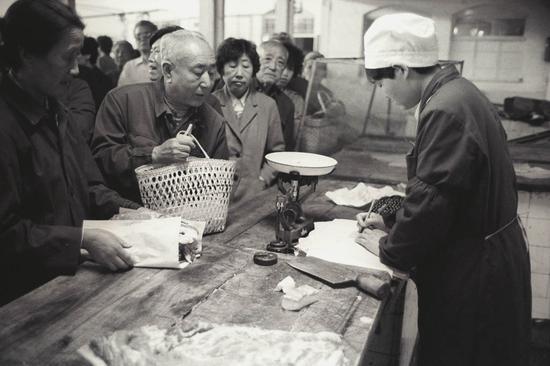 售货员秤完肉,当顾客交了钱和肉票后,在居民购货本上填写购买数量。