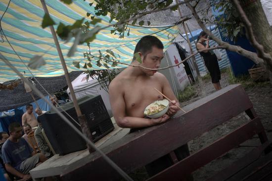 2008年,绵阳市安县精神病医院在地震中已经成为一片废墟。震后,医院内95名病人被安全的转移到大院中的帐篷内,一位病人躲在帐篷的角落里吃午餐。