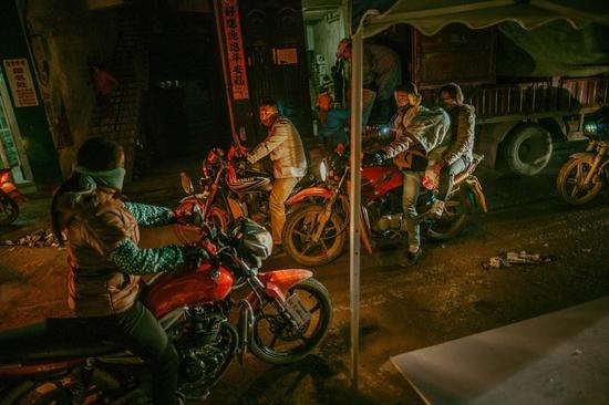 2016年,春节临近,中国广西一处乡村山路上交通繁忙,入夜,狭窄的村路上,骑着摩托车赶路的行人时常汇聚在一起。