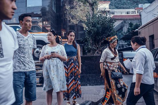 2016年,四川马尔康,一位身穿少数民族服装的女士走过街边的人群。
